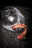 Pimentas de pimentão encarnados em um vidro em um fundo de madeira escuro Fotografia de Stock Royalty Free