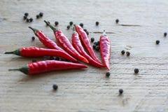 Pimentas de pimentão vermelho com pimentas pretas Imagens de Stock