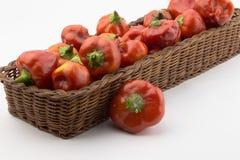 Pimentas de pimentão vermelho em uma cesta rústica em um ângulo isolada no whi Imagem de Stock Royalty Free