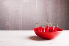 Pimentas de pimentão vermelho na placa em uma tabela de madeira clara no le Imagens de Stock