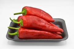 Pimentas de piment?o encarnados Muito fresco e brilhante, em placas pretas fotografia de stock