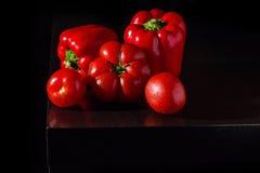 Pimentas de sino de Jucy e tomates frescos no fundo de madeira escuro Imagens de Stock Royalty Free
