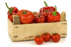 Pimentas doces e tomates vermelhos em uma caixa de madeira Foto de Stock
