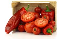 Pimentas doces e tomates vermelhos em uma caixa de madeira Fotos de Stock Royalty Free