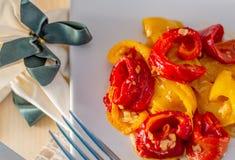Pimentas doces fritadas amarelas vermelhas cozinhadas em uma placa branca Guardanapo com uma curva fotos de stock