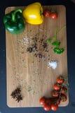 Pimentas e tomates verdes e amarelos no fundo de madeira Fotos de Stock