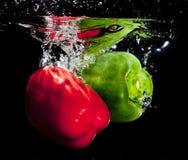 Pimentas que espirram na água Imagens de Stock