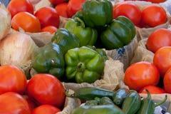 Pimentas, tomates, e cebolas no mercado de um fazendeiro Fotografia de Stock Royalty Free
