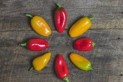 Pimentas vegetais amarelas e vermelhas no fundo de madeira Imagem de Stock Royalty Free