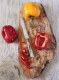 Pimentas vermelhas e amarelas na placa de madeira verde-oliva Fotos de Stock