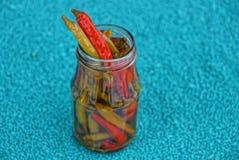Pimentas vermelhas e verdes em um frasco de vidro em um fundo azul Imagens de Stock Royalty Free