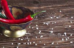 Pimentas vermelhas e verdes em um fundo de madeira Imagens de Stock Royalty Free