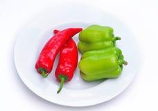 Pimentas vermelhas e verdes em uma placa branca Imagem de Stock Royalty Free