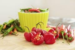 Pimentas vermelhas e verdes em uma placa de desbastamento Fotos de Stock Royalty Free