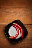 Pimentas vermelhas na placa cerâmica preta que está na madeira marrom Fotografia de Stock
