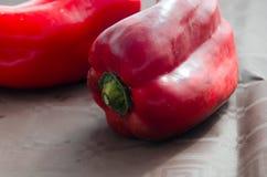 Pimentas vermelhas, na tabela com toalha de mesa marrom foto de stock royalty free