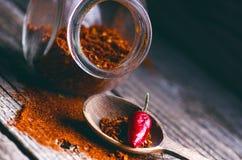 Pimentas vermelhas, picantes em uma colher de madeira Vegetal em uma tabela escura, de madeira Conceito do alimento quente Imagens de Stock Royalty Free