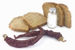 Pimentas vermelhas secadas, pão cortado e sal Fotos de Stock