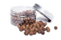 Pimento spice dry seeds in transparent plastic jar Stock Photo