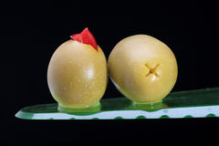 Pimento stuffed green olives on black. Side and bottom view of two green salad olives stuffed with red pimento on black background Stock Photos