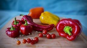 Pimentos alaranjados amarelos vermelhos maduros frescos, colheita cultivado em casa do outono Imagem de Stock