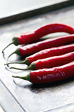 5 piments rouges sur une plaque de cuisson Photo stock
