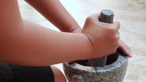 Piments thaïlandais et ail martelant en mortier en pierre avec le pilon Femme préparant la sauce pour l'igname thaïlandaise de To banque de vidéos
