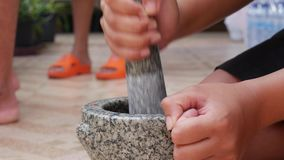 Piments tha?landais et ail martelant en mortier en pierre avec le pilon Femme pr?parant la sauce pour l'igname tha?landaise de To clips vidéos