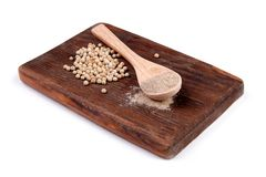 Pimienta blanca de tierra en una cuchara de madera en un tablero de madera Imagen de archivo libre de regalías