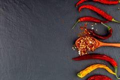 Pimienta de chile roja y amarilla secada En un fondo negro de piedra Foto de archivo libre de regalías