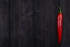 Pimienta de chile rojo en el fondo de madera oscuro, cierre para arriba Imagen de archivo