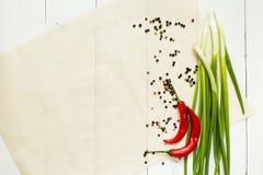 Pimienta de chile rojo y cebolla verde con las especias en un fondo de madera blanco, visión superior Espacio para un plato en un imagen de archivo libre de regalías