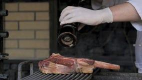 Pimienta del cocinero el filete en el fuego almacen de metraje de vídeo