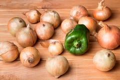 Pimienta dulce verde y algunas cebollas en superficie de madera Fotos de archivo libres de regalías