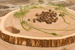 Pimienta inglesa, eneldo y ensalada en el corte de madera Imágenes de archivo libres de regalías