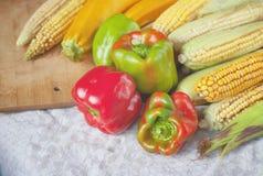 Pimienta, maíz y calabacín en un mantel de lino Fotografía de archivo