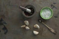Pimienta negra en mortero y maja con el cuenco de sal y de ajo Fotos de archivo