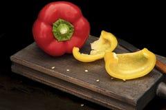 Pimienta roja con los pedazos de pimienta amarilla imagen de archivo