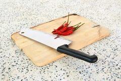 Pimienta roja en un cuchillo de madera de la pizca de la tabla de cortar Foto de archivo libre de regalías