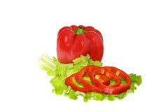 Pimienta roja y rebanadas menudas en una lechuga de hoja verde Imagen de archivo
