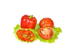Pimienta roja y tomate con las rebanadas en las hojas de la lechuga Imagen de archivo