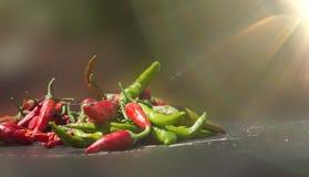 Pimienta roja y verde en fondo oscuro del tablero Imagen de archivo