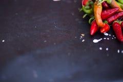 Pimienta roja y verde en fondo oscuro del tablero Foto de archivo
