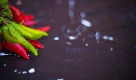 Pimienta roja y verde en fondo oscuro del tablero Imagen de archivo libre de regalías