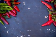 Pimienta roja y verde en fondo oscuro del tablero Fotografía de archivo