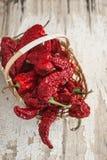 Pimienta secada al sol roja una cesta en la tabla de madera Imágenes de archivo libres de regalías