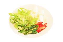 Pimienta verde, pimienta roja y rebanadas de la cebolla en una placa Imagen de archivo