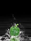 Pimienta verde que salpica el agua Fotografía de archivo libre de regalías