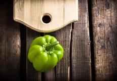 Pimienta verde y tabla de cortar en la tabla de madera Imágenes de archivo libres de regalías