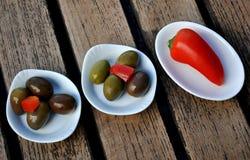 Pimienta y aceitunas en pequeños potes Fotos de archivo